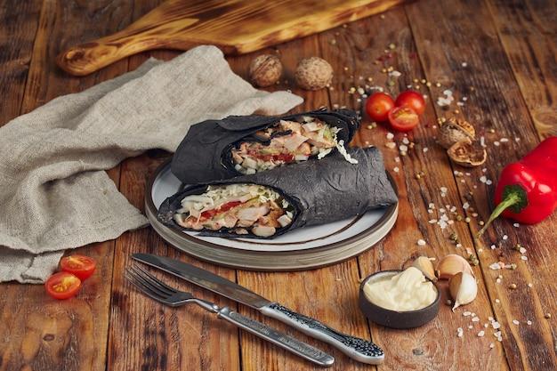 ドネルケバブ(シャワルマまたはドネルラップ)。木製のテーブルにトマト、グリーンサラダ、ピーマンを添えたラヴァッシュのグリルチキン