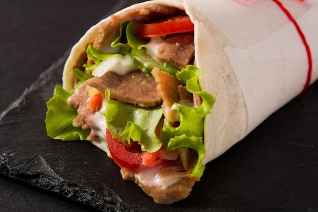 Doner kebab or shawarma sandwich on black slate surface close up
