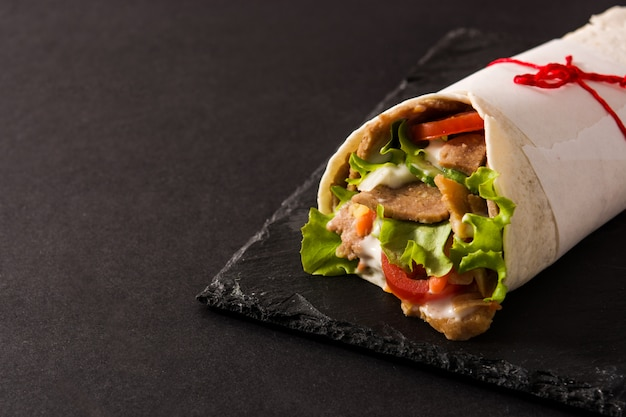 Doner kebab or shawarma sandwich on black slate surface copy space