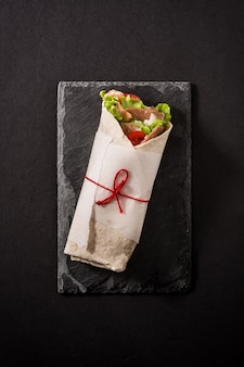 Doner kebab or shawarma sandwich on black slate surface. top view