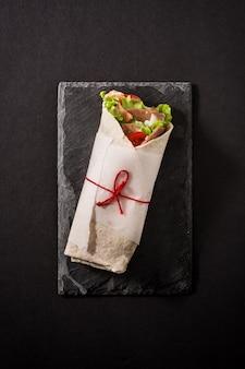 Doner kebab or shawarma sandwich on black slate surface. top view