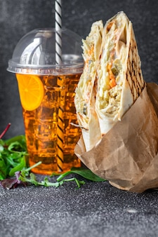 Doner kebab shawarma sandwich roll or burrito meat vegetables sauce taco