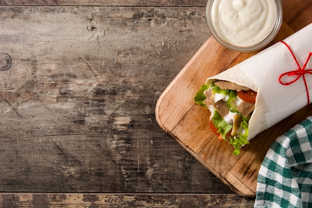Doner kebab or shawarma sandwich on wooden table top view copy space