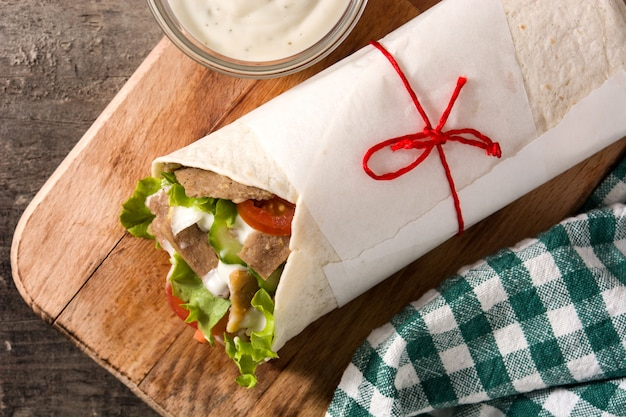 Doner kebab or shawarma sandwich on wooden table top view