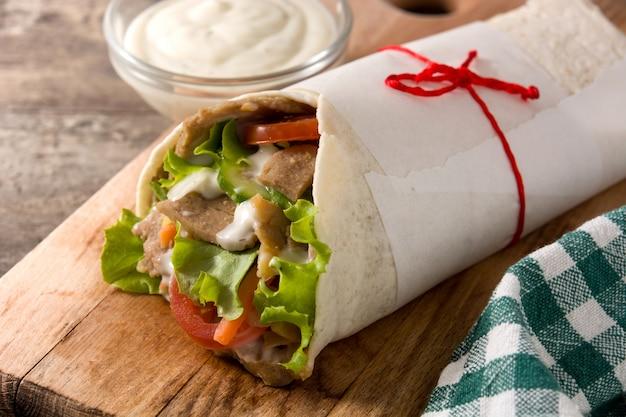 Doner kebab or shawarma sandwich on wooden table.