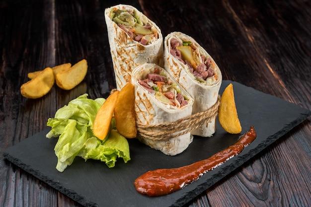 Донер кебаб, шаурма с деревенским картофелем и капустой на деревянном текстурированном фоне