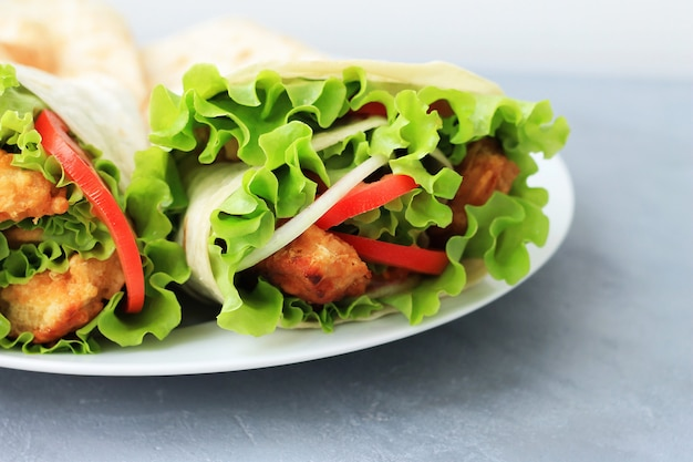 Doner kebab on a white plate. shawarma with meat, onions, salad and tomato on gray background.