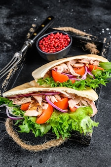 Doner kebab with grilled chicken meat and vegetables in pita bread on a wooden tray.