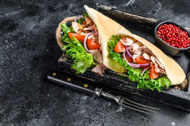 Doner kebab with grilled chicken meat and vegetables in pita bread on a wooden tray