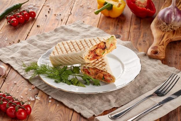 Донер кебаб с мясом, овощами и соусом, деревянный фон