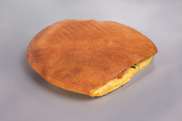 Doner in a round flatbread on a gray surface.