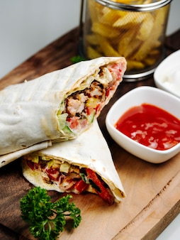 Doner wrapped in lavash with side fries and ketchup