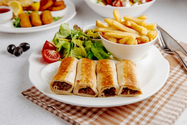 Doner wrapped in lavsh with fries on plate
