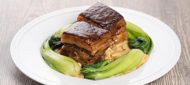 緑のブロッコリー野菜、伝統的なお祭り料理と美しい青いプレートの東坡肉(東坡肉)。