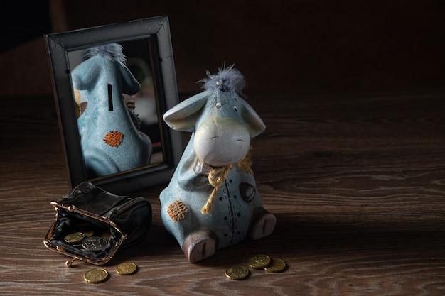 거울에 비친 당나귀 모양의 돼지 저금통, 동전 지갑, 은퇴 금융 개념.
