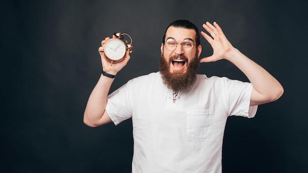 遅れないでください、目覚まし時計を持っているあごひげと眼鏡を持った驚いた男