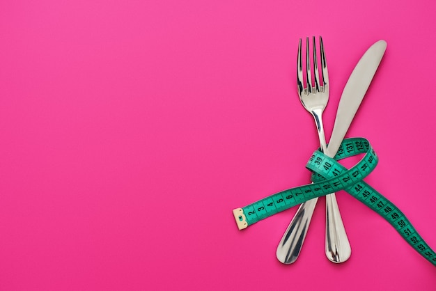 Dont eat too much. knife and fork crossed, connected by measure tape isolated on pink background