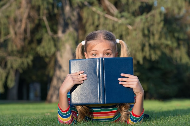 Dont judge book by its cover. adorable small child cover face with book. cute little girl read book on green grass. great eye for good book.