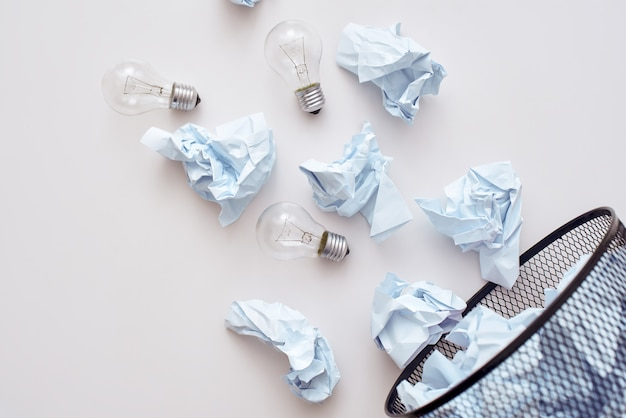このゴミを混ぜないでください。ごみの分別の概念。ごみ箱に落ちるしわくちゃの紙とランプ