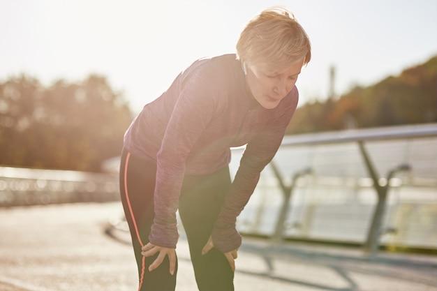 疲れて疲れているように見えるスポーツウェアのアクティブな成熟した女性が休憩した後、それをやり過ぎないでください