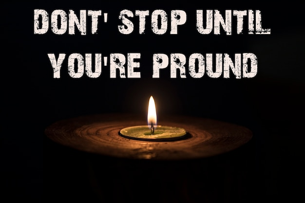 Dont' stop until you're pround - white candle with dark background - in a wooden candlestick.