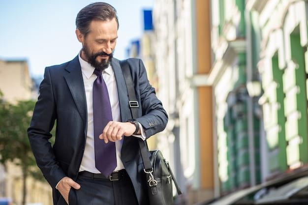 Не тратьте время зря. веселый взрослый бизнесмен, глядя на наручные часы, стоя на улице