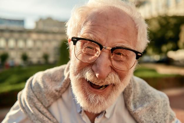 カメラを見て眼鏡をかけたハンサムなひげを生やした年配の男性の古い肖像画を取得することを心配しないでください