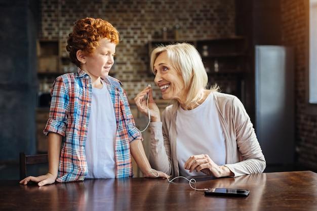 괜찮아요. 그녀의 빨간 머리 손자를보고 음악 재생을 듣기 위해 귀에 이어폰을 꽂고 활짝 웃고있는 빛나는 노인 여성.