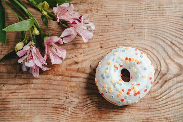 나무 배경에 도넛과 알스트로메리아 꽃. 위에서 볼 수 있습니다. 꽃과 나무 테이블에 흰색 유약과 사탕 도넛.