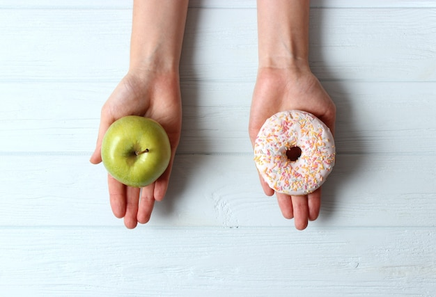 여성의 손에 든 도넛과 사과 건강하고 건강에 해로운 음식 선택