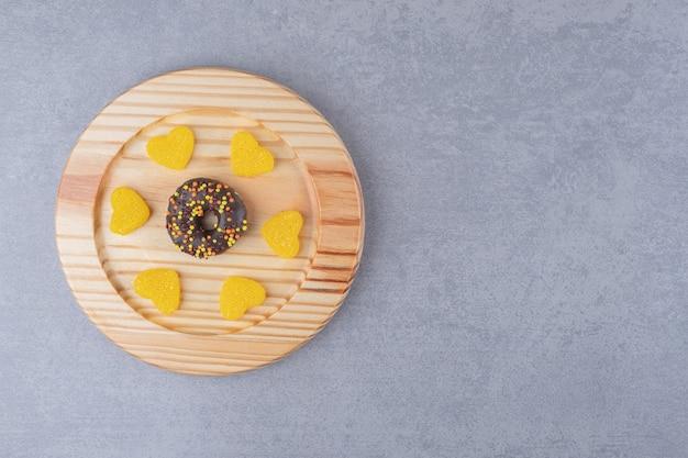 Пончик и мармелады на блюде на мраморной поверхности