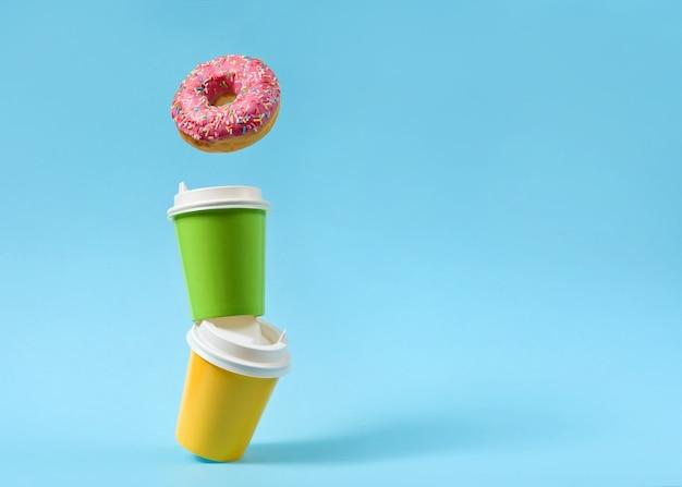 복사 공간 파란색 표면에 도넛과 종이 컵