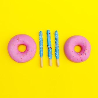 노란색 배경에 도넛과 달콤한 막대기. 플랫 레이 푸드 아트