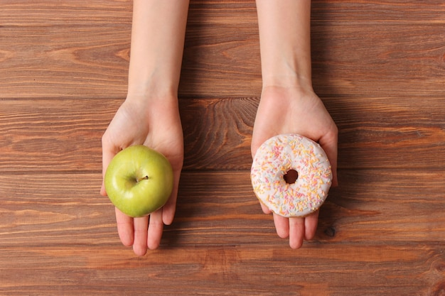 Donut and apple in female hands healthy and unhealthy food choice
