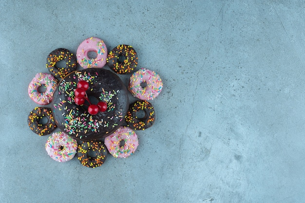 Donut arrangement decorated with a christmas berry ornament on marble.
