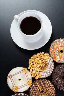 Donut and coffee on the black background