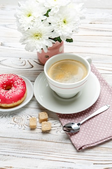 Donut and coffee, flowers on wooden background