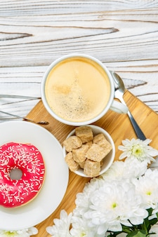 Donut and coffee on wooden background