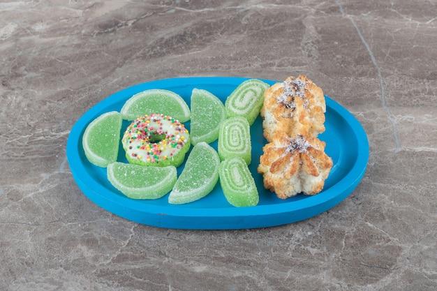 Una ciambella, biscotti e marmellate su un piccolo piatto su una superficie di marmo