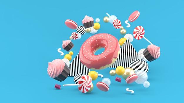ドーナツ、カップケーキ、マカロン、キャンディーが青のカラフルなボールの間に浮かんでいます。 3dレンダー