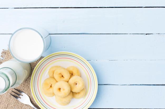 木製の空の青のテーブルにドーナツのデザートと牛乳瓶とミルクガラス。