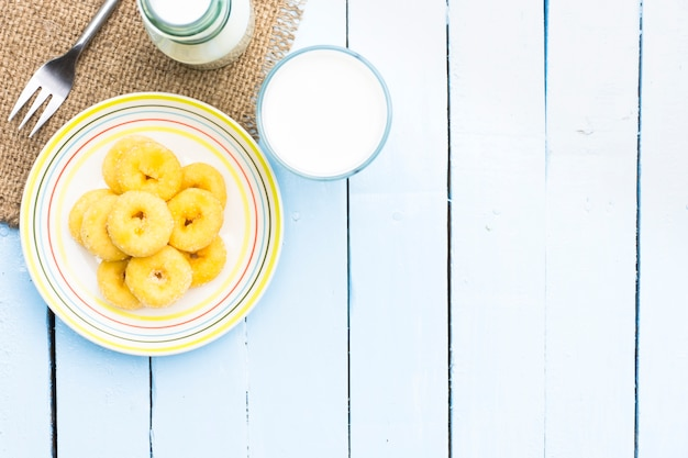 Donut dessert and milk bottle and milk glass on wooden sky blue table.