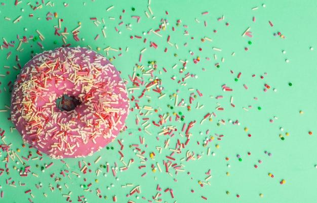 緑の背景にさまざまな色のドーナツ(ドーナツ)に色とりどりのお祝い砂糖を振りかけます。休日とお菓子、子供のためのベーキング、砂糖の概念