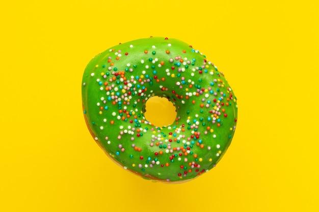 노란색 표면에 고립 된 뿌리와 도넛 녹색