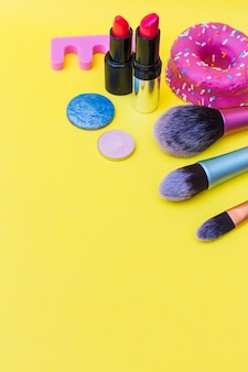 Donut; makeup brush; lipstick; and eye shadows on yellow background