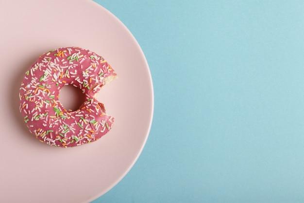 青色の背景にピンクのプレートにドーナツ。