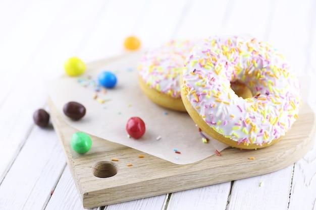 木製の白い背景の上のドーナツと甘い装飾品の散乱