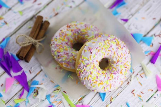 나무 흰색 배경에 도넛과 달콤한 장식품이 흩어져 있습니다.