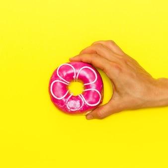 노란색 배경에 도넛입니다. 플랫 레이 패스트 푸드 아트. 도넛 애호가 개념