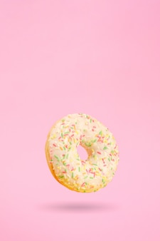 Donut on pink with shadow hanging in the air